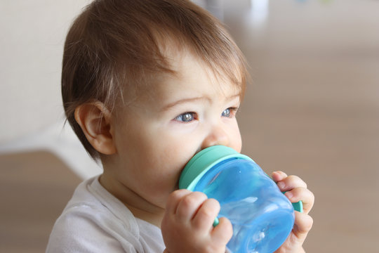 Cute little baby holding his blue bottle and drinking water from it at home, close-up