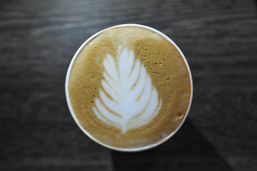 A cup of fragrant and beautiful coffee is on the table. Picture on foam - leaf