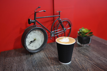 A cup of fragrant and beautiful coffee stands on a table on the background of a red wall and a small figure bicycle. Picture on foam - leaf