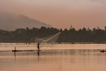 Beautiful landscape and fisherman spreads the web in golden hours of water dam
