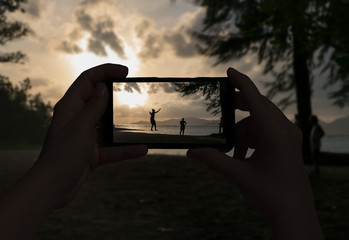 Female hand taking picture of walking people on a rope on the island of La Digue. Seychelles