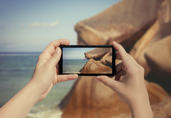 Female hand taking picture of La Digue island on mobile phone. Picture of Seychelles island on smart phone