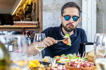 Young man eating vegetable salad and pulpo a la Gallega with potatoes. Galician octopus dishes. Famous dishes from Galicia, Spain.