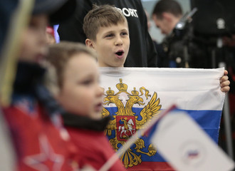 A boy holds the national flag during a welcoming ceremony for Russian athletes turning back from the Pyeongchang 2018 Winter Olympics, at Sheremetyevo International Airport outside Moscow