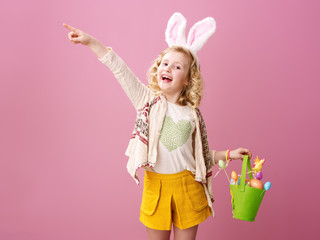 child pointing at something showing festive Easter eggs basket