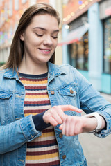Woman Walking On City Street Using Smart Watch