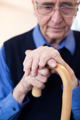 Sad Senior Man Sitting In Chair Holding Walking Cane