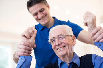 Male Nurse Assessing Senior Stroke Victim By Raising Arms