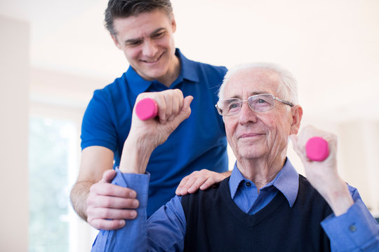 Physiotherapist Helping Denopr Man To Lift Hand Weights