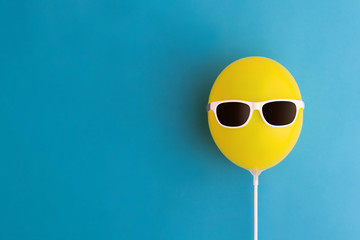 Yellow balloon with sunglasses Wall mural