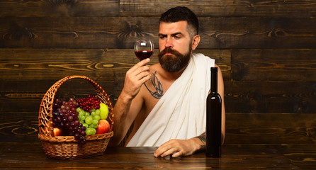 God of wine with serious face sits by wine bottle