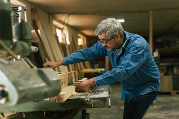 middle aged carpenter working in his workshop