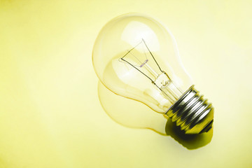 Light bulb on glossy reflective yellow glass surface.