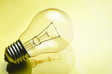 Light bulb on yellow glossy reflective glass surface. Technology background.