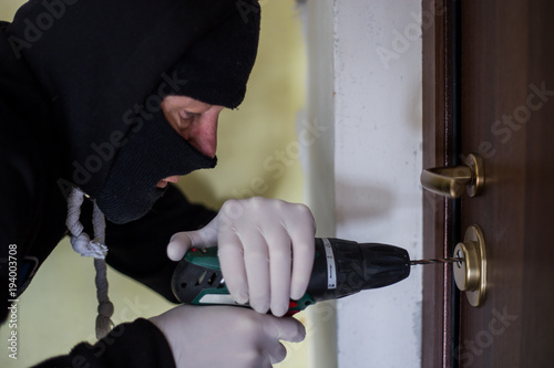 Crime Robbery Masked Thief Burglar Trying To Break Into A Flat Drill In The Hands Cap On Head And Gloves That There Are No