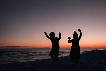 Silhouette siblings dancing at beach against sky during sunset