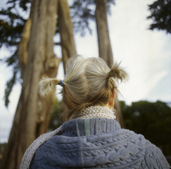 Rear view of woman with pigtails standing by trees against cloudy sky