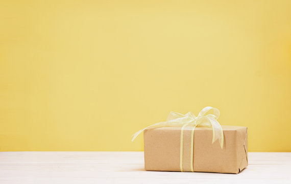 Yellow gift box on wooden table