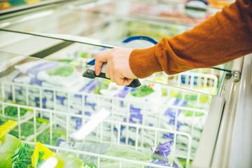 man get frozen food from fridge in store