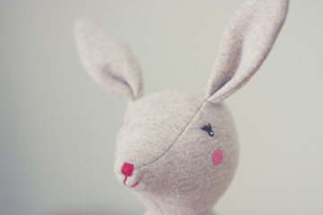 Cute toy bunny close up with natural background. Single object, light beige. Shallow depth of field. Easter bunny. Minimalistic. Matte vintage filter.
