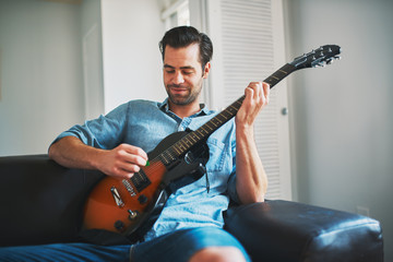 man playing electric guitar on sofa at home