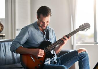 smiling handsome man having fun playing guitar