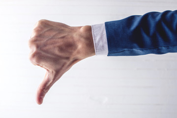 Male hand of businessman in suit showing thumb down