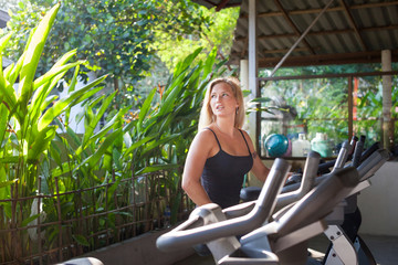 Woman at the gym exercising on the trainer machines. Fitnessat at the tropical gym. Cardio workout..