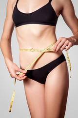 Slim fit happy young woman with measure tape measuring her waist with black underwear