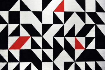 Piękny dywan, geometryczne wzory, białe, czarne i czerwone.