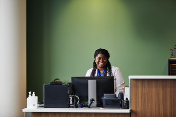 Portrait of smiling doctor sitting against green wall at hospital reception