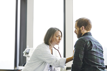 Serious female doctor examining male patient