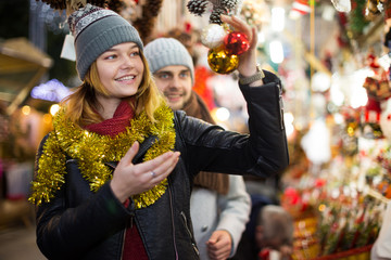 Positive young couple buying decoration at Christmas Fair