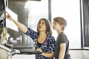Female doctor showing computer monitor to boy in a hospital Wall mural