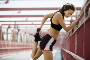 Sporty Young Woman Stretching Leg On Bridge