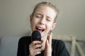 Cute little girl singing karaoke at home.