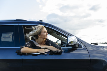 Happy young woman looking out of car window during road trip Wall mural