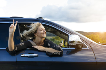 Smiling young woman gesturing peace sign while looking out of car window during road trip
