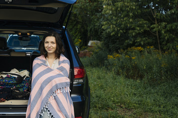 Portrait of smiling young woman wrapped in blanket sitting in car trunk during road trip