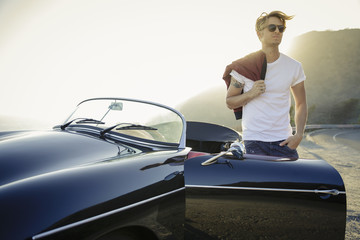 Handsome Man Standing By Convertible at dusk
