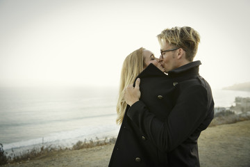 Couple Embracing While Kissing  near ocean view
