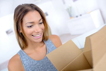 attractive woman opening a cardboard box