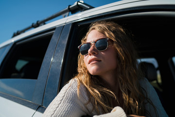 Woman Wearing Sunglasses While Looking Through Car Window