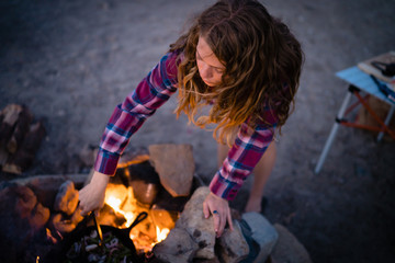 Woman cooking food in campfire at campsite