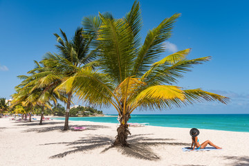 Caribbean tropical beach destination in Barbados, cruise activity. Woman sunbathing relaxing tanning under palm tree on sand on Dover beach, famous resort tourist attraction.