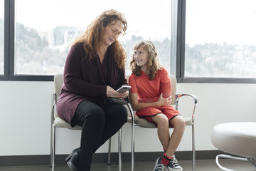 Girl looking at mother using mobile phone while sitting in waiting room of hospital
