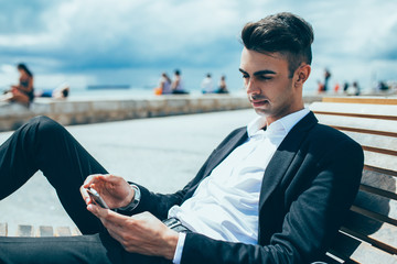 Serious man texting sms while resting on shore