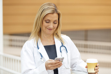 Smiling mature female doctor using mobile phone while holding coffee cup in hospital