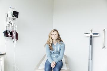Teenage girl sitting on hospital bed in examination room