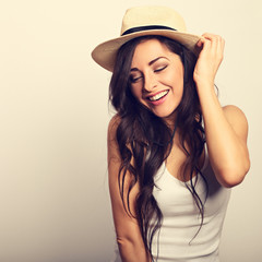 Beautiful long hair laughing woman in white top and straw hat looking happy. Toned vintage portrait